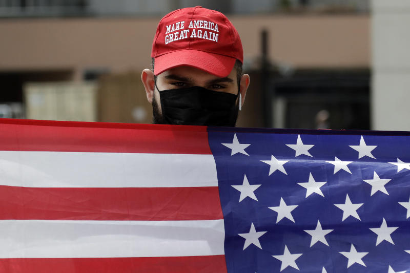 Sevag Demirjian, a supporter of President Trump, waves an American flag at passing demonstrators during a protest outside of the Edward R. Roybal Federal building Tuesday, March 31, 2020, in Los Angeles. Demonstrators across California coordinated efforts in a car-based protest to demand the release of immigrants in California detention centers over concerns over the COVID-19 pandemic. (AP Photo/Marcio Jose Sanchez)