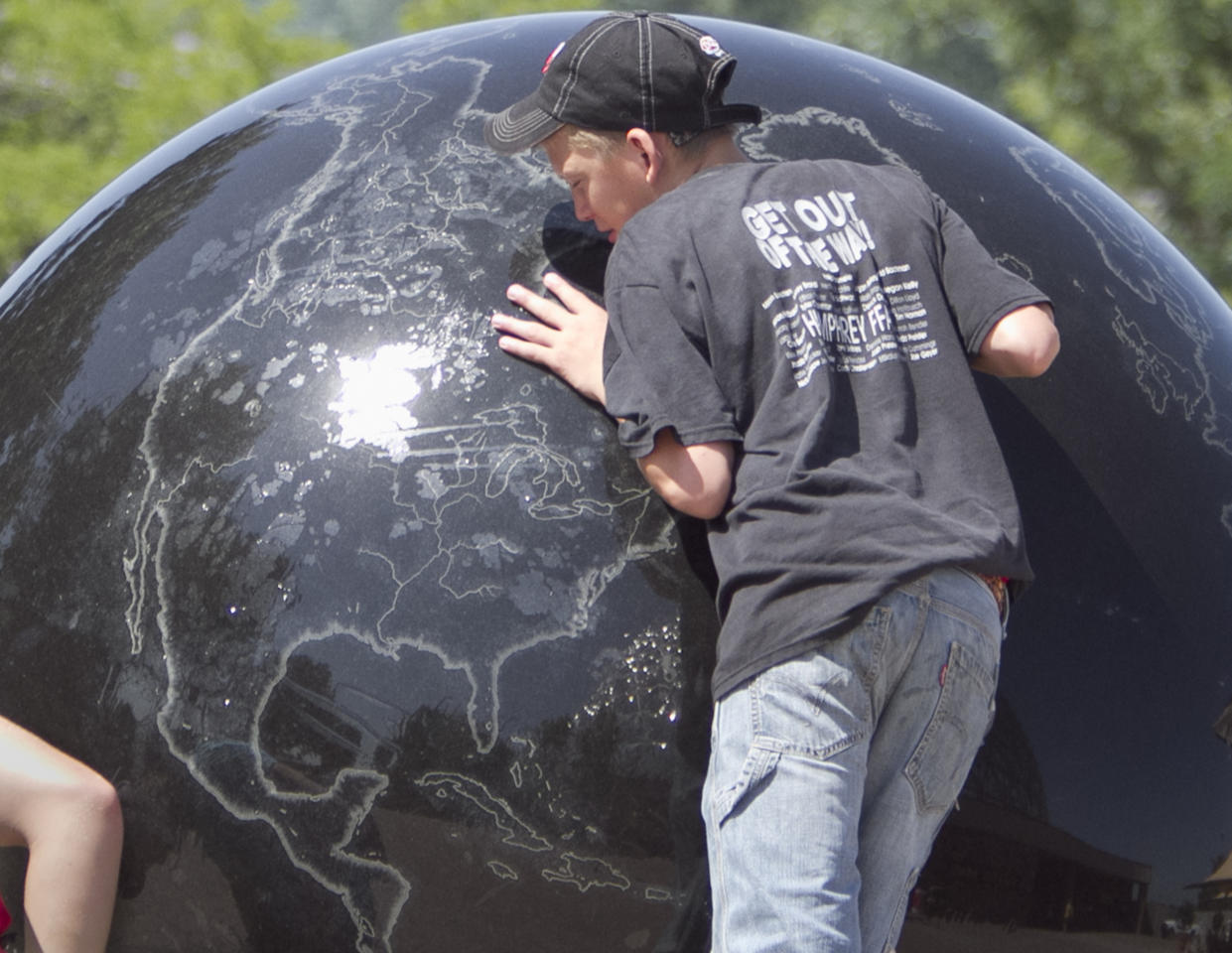 "A visitor to the Henry Doorly Zoo in Omaha, Neb., leans against a sculpture of Planet Earth, with the sun reflecting off the center of the American Continent, Tuesday, July 19, 2011. Heat advisories and warnings were in place in 17 states, from Texas to Michigan, as temperatures and humidity combined to make being outside uncomfortable for millions. One National Weather Service forecaster called the heat wave ""unrelenting"" and said sweaty residents shouldn't expect any relief soon: A so-called ""heat dome"" over the region isn't moving much. (AP Photo/Nati Harnik)"