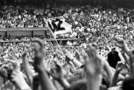 General view of fans holding a U2 flag above the crowds in the audience on The Joshua Tree Tour at Feyenoord Stadion, De Kuip, Rotterdam ,Netherlands, 10th July 1987. (Photo by Rob Verhorst/Redferns)