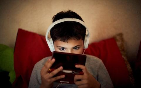 A child playing games on smartphone - Credit: Paco Navarro