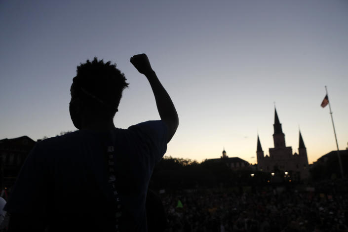 A man raises his fist during a rally outside Jackson Square in New Orleans, Friday, June 5, 2020, protesting the death of George Floyd, a black man who was in police custody in Minneapolis. (AP Photo/Gerald Herbert)