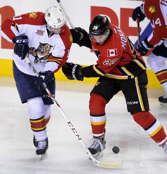 Florida Panthers' Jonathan Huberdeau, left, battles for the puck with Calgary Flames' Sean Monahan during the first period of an NHL hockey game, Friday, Nov. 22, 2012 in Calgary, Alberta. (AP Photo/The Canadian Press, Larry MacDougal)