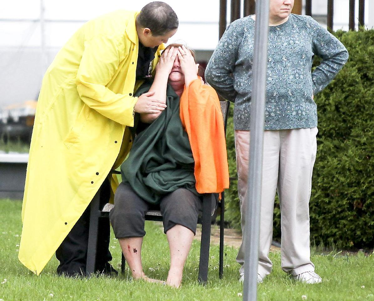 A woman in Proctor, Minn. reacts after the report of a boy was swept away into a sinkhole on Lawn Street in Proctor Wednesday, June 20, 2012. The boy was later found alert and conscious after being swept through six block of culverts by the floodwaters. Record rainfall occurred in the Duluth, Minn., area Wednesday, with some areas receiving seven to 10 inches of rain in the past 24 hours. (AP Photo/The Duluth News-Tribune, Clint Austin)