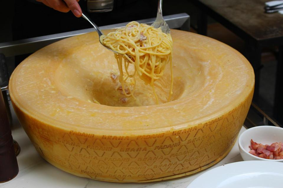 Hot dishes such as the pasta and the cold dish like the salad are tossed in two different cheese wheels. (Photo: Yahoo Singapore)