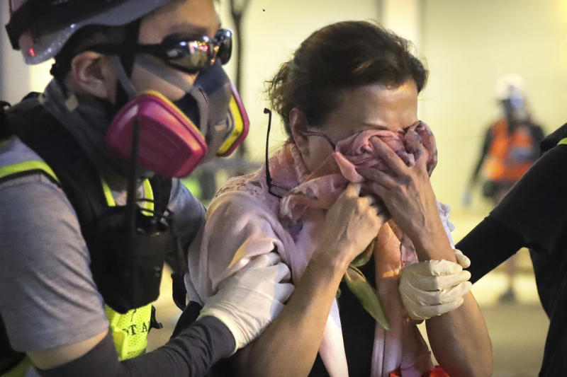 A volunteer medic escorts a woman affected by tear gas during a protest in Hong Kong, Saturday, Nov. 2, 2019. Hong Kong riot police fired multiple rounds of tear gas and used a water cannon Saturday to break up a rally by thousands of masked protesters demanding meaningful autonomy after Beijing indicated it could tighten its grip on the Chinese territory. (AP Photo/Kin Cheung)