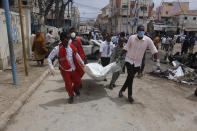 Medical personnel carry a body after a car bomb attack at a Presidential Palace checkpoint in Mogadishu, Somalia, Saturday Sept. 25, 2021. Police said a vehicle laden with explosives rammed into cars and trucks at a checkpoint leading to the entrance of the Presidential Palace, killing at least eight people. (AP Photo/Farah Abdi Warsameh)