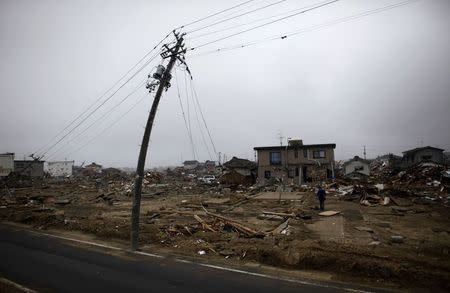 A man walks near a damaged power pole at an area that was devastated by the March 11 earthquake and tsunami, in Watari, Miyagi prefecture, in this April 22, 2011 file photo.  REUTERS/Toru Hanai/Files