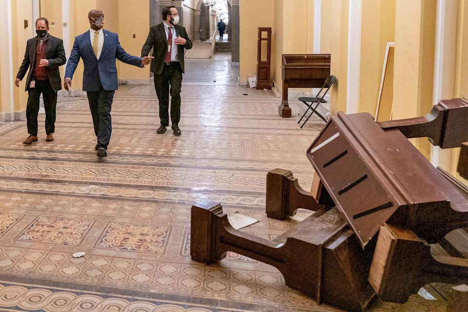 <p>Senator Tim Scott, second from left, walks past damage in the early morning hours after protesters stormed the Capitol in Washington</p> (AP)