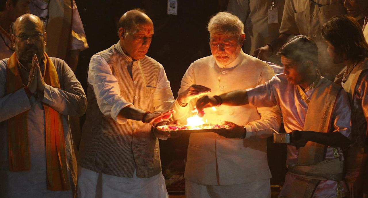 Hindu nationalist Bharatiya Janata Party (BJP) leader and India's next prime minister Narendra Modi, second right, and BJP President Rajnath Singh, second left, perform evening rituals with the help of a Hindu priest, as leader Amit Shah folds his hands in respect on the banks of the River Ganges in Varanasi, an ancient city revered by millions of devout Hindus, India, Saturday, May 17, 2014. Modi will be India's next prime minister, winning the most decisive victory the country has seen in more than a quarter century and sweeping the long-dominant Congress party from power, results showed Friday. An elaborately decorated platform was built for him to offer prayers on the banks of the river. Saffron flags fluttered above the flower bedecked platform and thousands of supporters and onlookers milled around to watch as Hindu priests chanted sacred verses and burnt incense. (AP Photo/Saurabh Das)