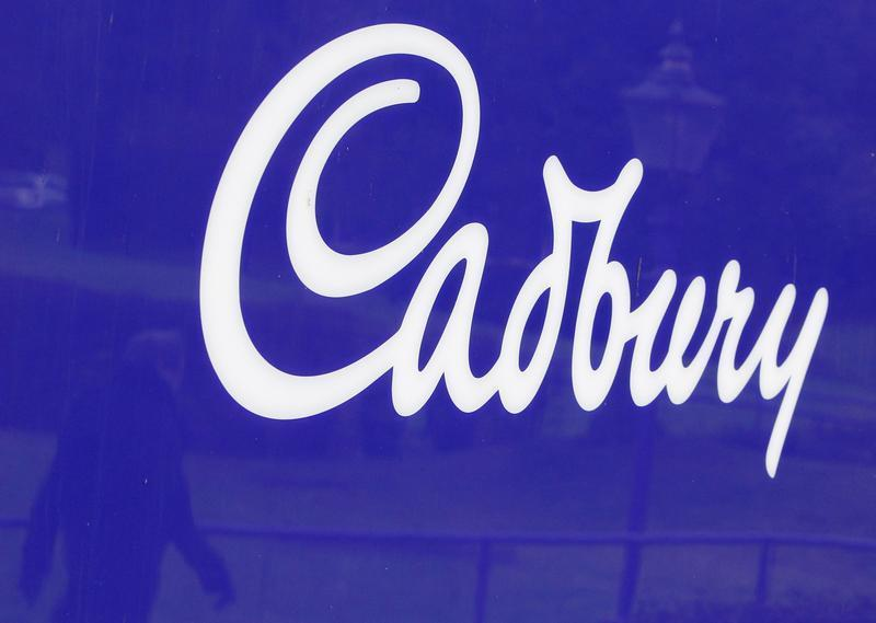 A man is reflected in a sign outside the Cadbury factory in Bournville, central England