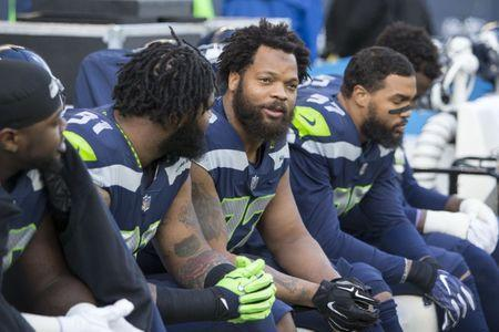 Dec 31, 2017; Seattle, WA, USA; Seattle Seahawks defensive end Michael Bennett (72) and teammates sit on the bench during the national anthem before kickoff against the Arizona Cardinals at CenturyLink Field. Mandatory Credit: Joe Nicholson-USA TODAY Sports
