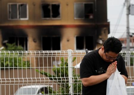 A man prays for victims in front of the torched Kyoto Animation building in Kyoto