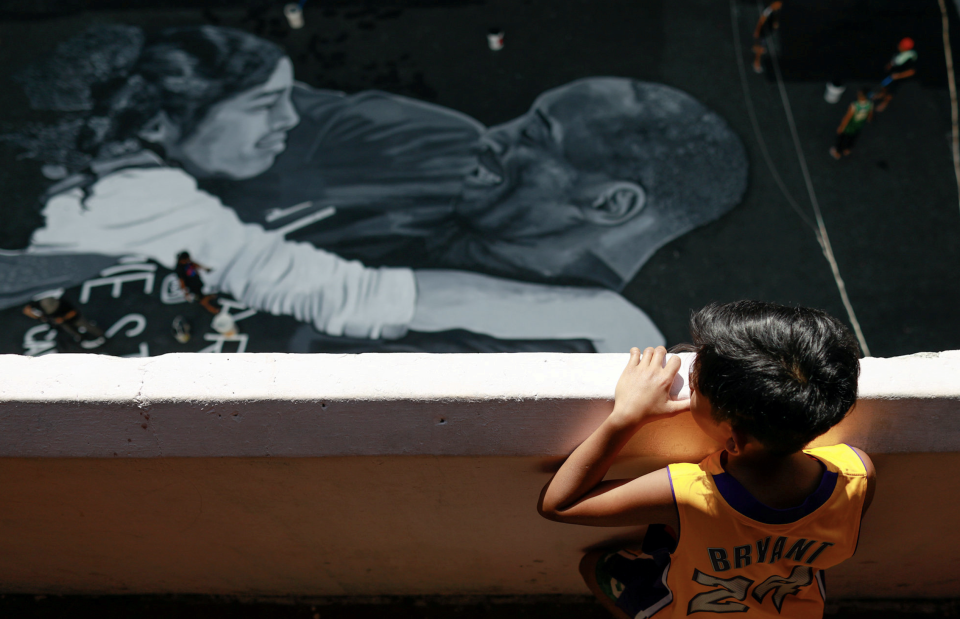 Ashly Muceros, a 10-year-old fan of Kobe Bryant, looks at a mural, painted in memory of him and his daughter Gianna hours after they died in a helicopter crash, on the basketball court of a housing tenement in Taguig City, Metro Manila, Philippines, January 28, 2020. (Photo: REUTERS/Eloisa Lopez)