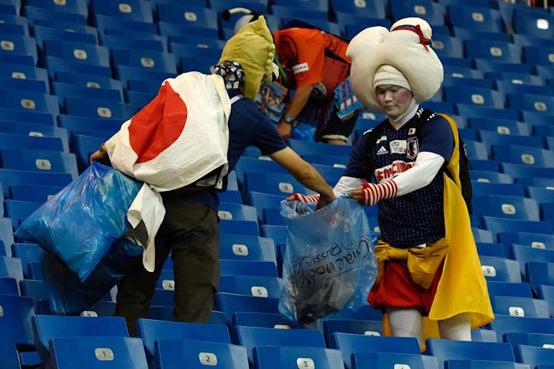 Helping: Japan supporters collect rubbish after the defeat (AFP/Getty Images)