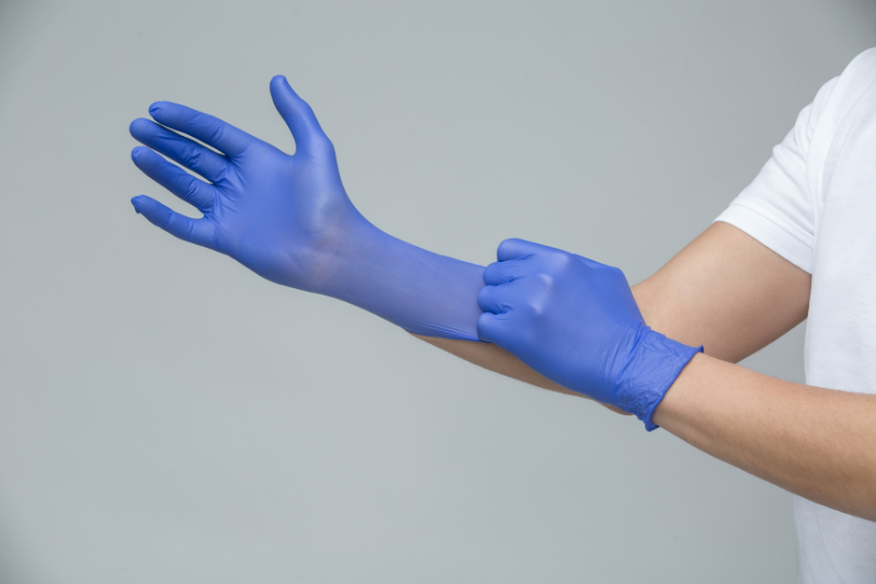 Person Putting on Disposable Gloves
