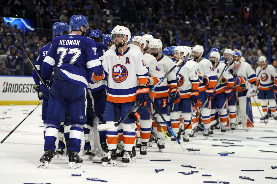 Tampa Bay Lightning defenseman Victor Hedman (77) and his teammates shake hands with New York Islanders right wing Josh Bailey, front right, and his teammates after Game 7 of an NHL hockey Stanley Cup semifinal playoff series Friday, June 25, 2021, in Tampa, Fla. Tampa won the final game 1-0. (AP Photo/Chris O'Meara)