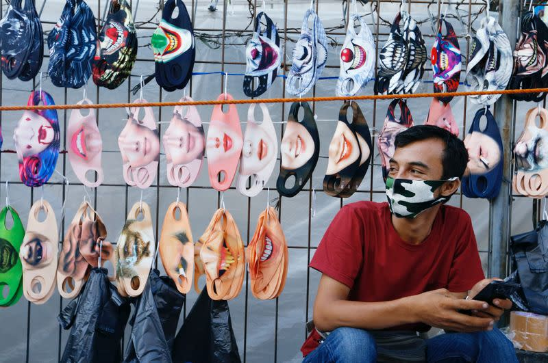 A vendor sits near a face design masks display at a traditional market, amid the coronavirus disease (COVID-19) outbreak, in Jakarta