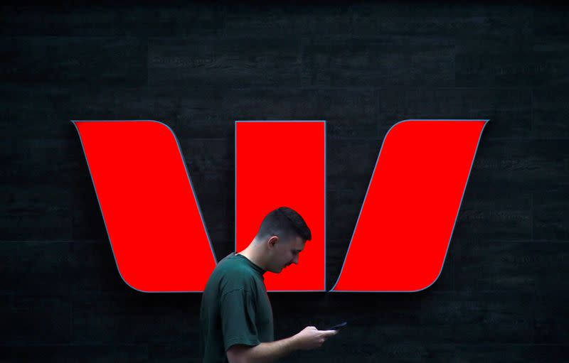 FILE PHOTO: A pedestrian looks at his phone as he walks past a logo for Australia's Westpac Banking Corp located outside a branch in central Sydney