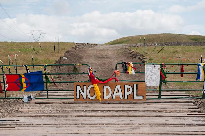 <p>Signs opposing the Dakota Access oil pipeline (DAPL) stand at the gate of a road where construction has been stopped for weeks due to protests near the Standing Rock Sioux Reservation, in Cannon Ball, N.D., on Sept. 7, 2016. (Photo: Andrew Cullen/Reuters) </p>