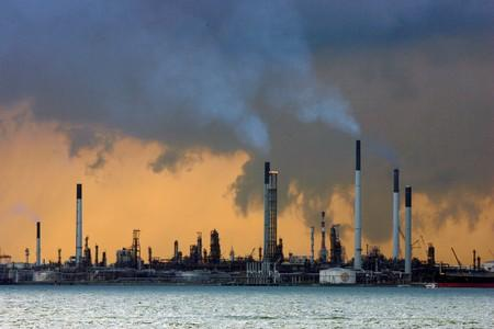 FILE PHOTO: Smoke billows from the towers of an oil refinery off the coast of Singapore