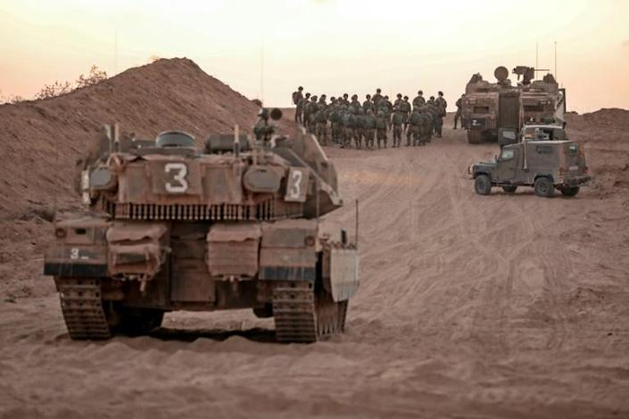 Israeli infantry soldiers gather next to tanks and an armoured personnel carrier near the Israeli border with the Gaza Strip on Sunday