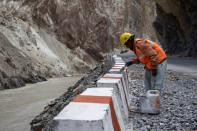 A labourer from the Border Roads Organisation (BRO) works on an under construction highway in the Ladakh region
