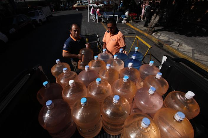 In this Jan. 4, 2014 photo, a vendor, right, prepares to fill his bicycle cart with 18-liter jugs of bottled water to sell to owners of street food stalls in Mexico City. Bad tap water accounts in part for Mexico being the highest consumer of bottled water and sweetened drinks. A law recently approved by Mexico City's legislators will require all restaurants to install filters, offering patrons free, apparently drinkable potable water that won't lead to stomach problems and other ailments. With an obesity epidemic looming nationwide, the city's health department decided to back the water initiative. (AP Photo/Marco Ugarte)