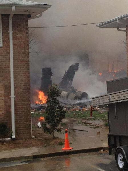 The burning fuselage of an F/A-18 Hornet lies smoldering after crashing into a residential building in Virginia Beach, Va., Friday, April 6, 2012. The Navy did not immediately return telephone messages left by The Associated Press, but media reports indicate the two aviators were able to eject from the jet before it crashed. They were being treated for injuries that were not considered life threatening. (AP Photo)