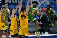 Oregon guard LJ Figueroa (12) passes around Iowa center Luka Garza (55) during the second half of a men's college basketball game in the second round of the NCAA tournament at Bankers Life Fieldhouse in Indianapolis, Monday, March 22, 2021. (AP Photo/Paul Sancya)