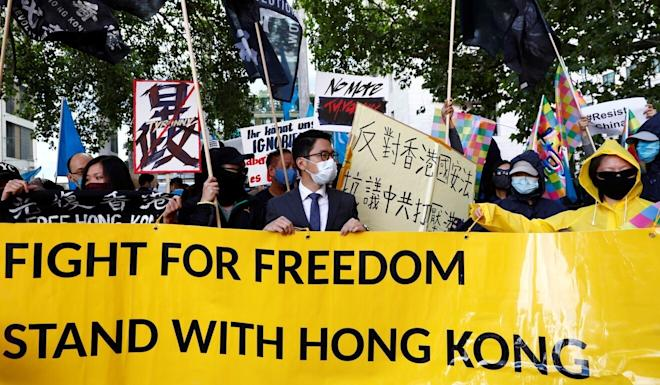 Hong Kong activist Nathan Law, wearing a face mask, holds a rally with other activist groups during China's foreign minister Wang Yi's visit in Berlin on Tuesday. Photo: Reuters