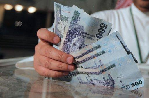 A man holds Saudi money in Riyadh on  July 24, 2012