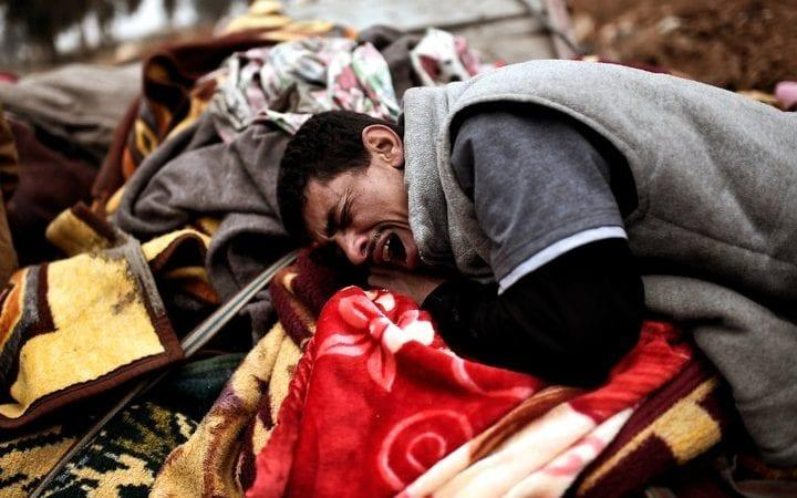 Relatives mourn as bodies of Iraqi residents of west Mosul killed in an airstrike targeting Islamic State  jihadists are placed and covered with blankets on carts on March 17, 2017.  - Credit: Getty