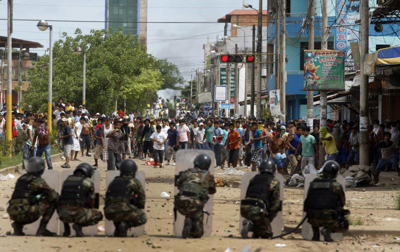 Police officers and miners clash during a protest in Puerto Maldonado, Peru, Wednesday, March 14, 2012. Thousands of illegal gold miners battled police for control of a regional capital in the Amazon basin on Wednesday and at least three people were killed by gunfire. The miners are fighting government efforts to regulate small-scale gold extraction, which is ravaging the rain forest, contaminating it with tons of mercury. (AP Photo/ Miguel Vizcarra)