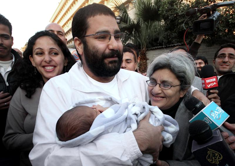 FILE - In this Sunday, Dec. 25, 2011 file photo, Egyptian prominent blogger Alaa Abdel Fattah, center, hugs his recently born son, Khaled, his mother Laila Soueif, and his sister Ahdaf Soueif, left, after his release, in Cairo, Egypt. Egypt's Islamist president makes good on vows of action against opponents, as the top prosecutor issues arrest warrants against five prominent activists and summons opposition politicians for questioning over weekend clashes between the Muslim Brotherhood and protesters. (AP Photo/ Amr Hafez, File)