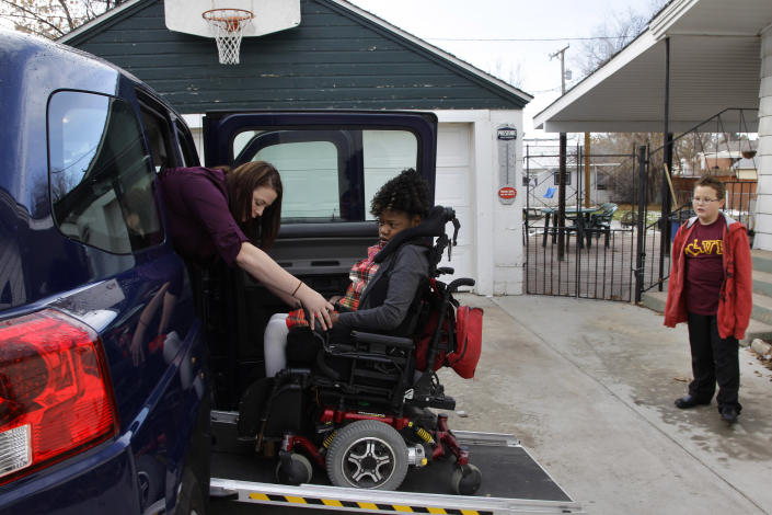 In this Nov. 14, 2012 photo, Brooke Croteau, an assistant to Carrie Ann Lucas, a disabled mother of four disabled adopted children, helps Adrianne, 13, one of Lucas' children, into a vehicle as the family leaves their home in Windsor, Colo., to attend an adoption hearing. Anthony, 11, the intellectually-disabled adopted son of Lucas, is pictured at right. (AP Photo/Brennan Linsley)