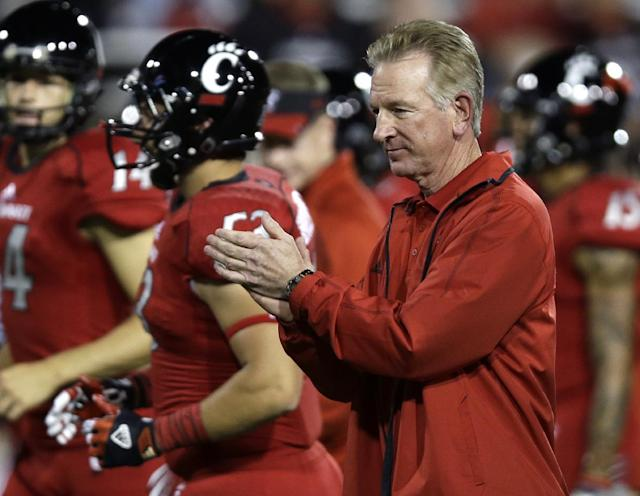 Cincinnati coach Tommy Tuberville cheers on his players at the start of an NCAA college football game against Temple, Friday, Oct. 11, 2013, in Cincinnati. (AP Photo/Al Behrman)
