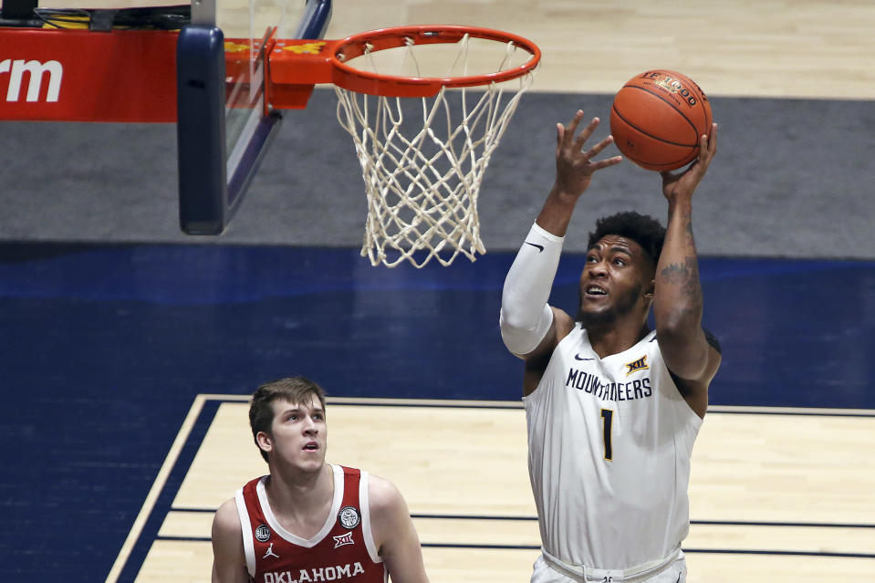 West Virginia forward Derek Culver (1) shoots while defended by Oklahoma guard Austin Reaves (12) looks on during the first half of an NCAA college basketball game Saturday, Feb. 13, 2021, in Morgantown, W.Va. (AP Photo/Kathleen Batten)