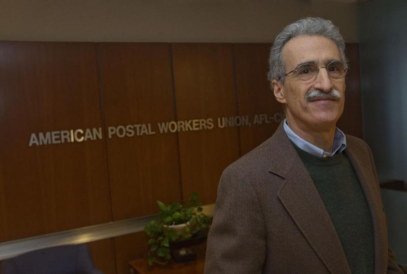 "Mark Dimondstein, president of the American Postal Workers Union poses for a photo at their Washington headquarters, Friday, Jan. 17, 2014. The opening of Postal Service retail centers in dozens of Staples stores around the country is being met with threats of protests and boycotts by the agency's unions. The new outlets are staffed by Staples employees, not postal workers, and labor officials say that move replaces good-paying union jobs with low-wage, nonunion workers. ""It's a direct assault on our jobs and on public postal services,"" said Mark Dimondstein, president of the 200,000-member American Postal Workers Union. (AP Photo/Pablo Martinez Monsivais)"