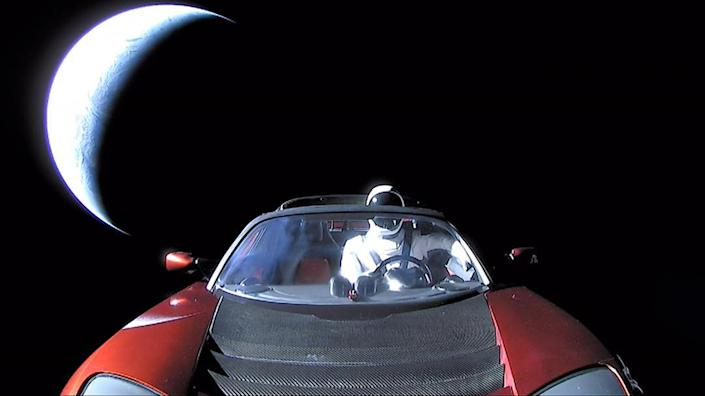 """The last photo of """"Starman"""" in Elon Musk's red Tesla Roadster as it flies toward Mars orbit. Earth is the bright crescent seen in the background."""