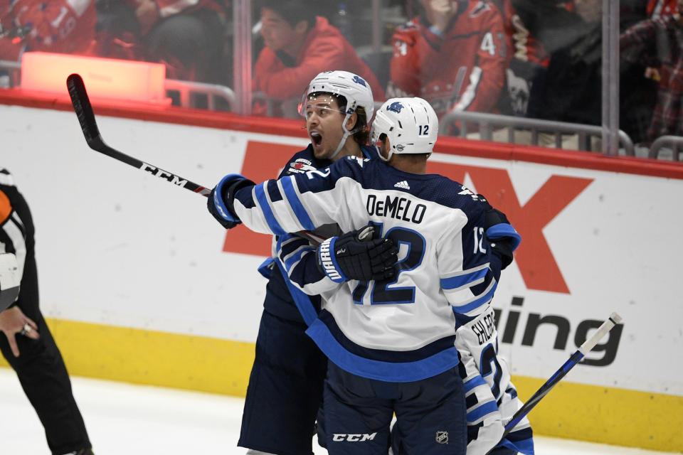 Winnipeg Jets center Mark Scheifele, left, celebrates his goal with defenseman Dylan DeMelo (12) during the third period of the team's NHL hockey game against the Washington Capitals, Tuesday, Feb. 25, 2020, in Washington. The Capitals won 4-3 in a shootout. (AP Photo/Nick Wass)