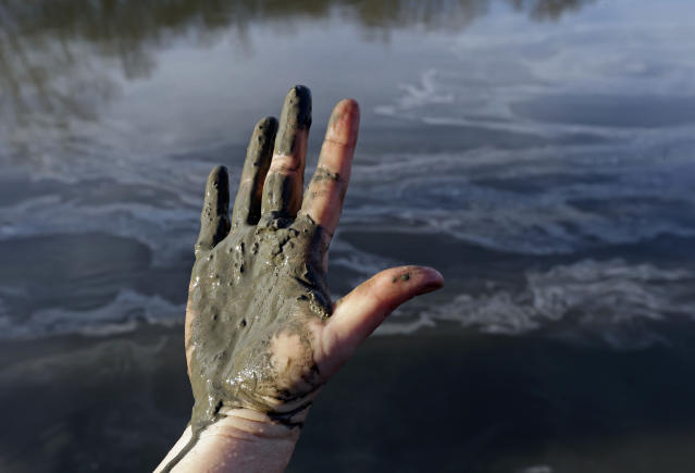 Amy Adams, North Carolina campaign coordinator with Appalachian Voices, shows her hand covered with wet coal ash from the Dan River swirling in the background, in Danville, Va., in 2014. (Photo: Gerry Broome/AP)