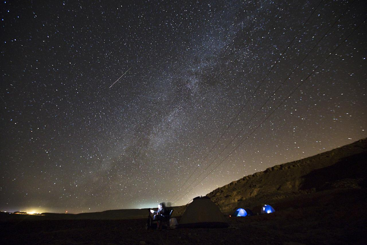 A meteor streaks across the sky in the early morning as people watching during the Perseid meteor shower in Israel.