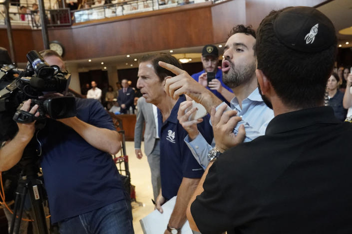 An unidentified man is taken out as he interrupts Florida Gov. Ron DeSantis, Monday, June 14, 2021, at the Shul of Bal Harbour, a Jewish community center in Surfside, Fla. DeSantis visited the South Florida temple to denounce anti-Semitism and stand with Israel, while signing a bill into law that would require public schools in his state to set aside moments of silence for children to meditate or pray. (AP Photo/Wilfredo Lee)