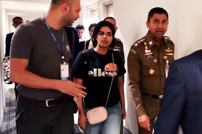 This handout picture taken and released by Thai Immigration Bureau on January 7, 2019 shows 18-year-old Saudi woman Rahaf Mohammed al-Qanun escorted by the Thai immigration officer and United Nations High Commissioner for Refugees (UNHCR) officials at the Suvarnabhumi international airport in Bangkok.