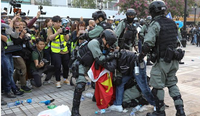 Police grapple with a protester in Edinburgh Place. Photo: May Tse