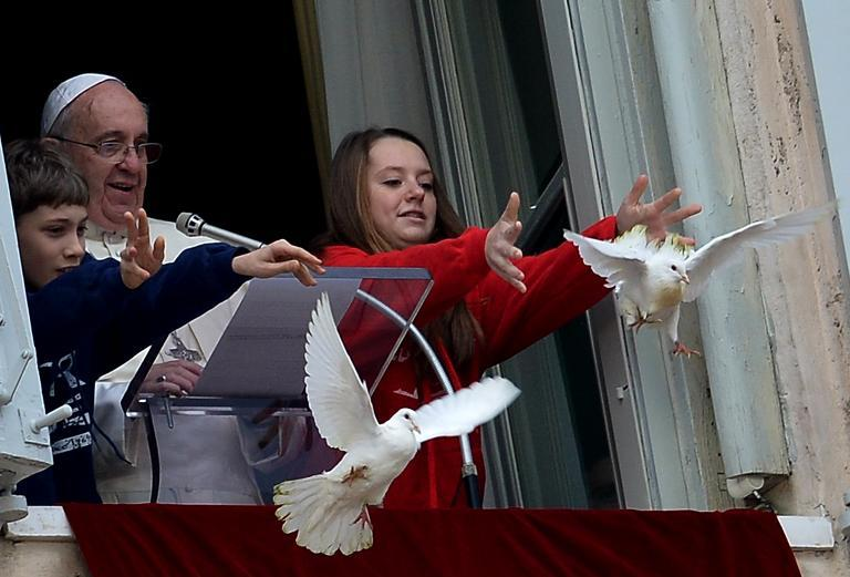 Children release white doves next to Pope Francis from the window of his private apartments during his Sunday Angelus prayer at St Peter's square on January 26, 2014 at the Vatican