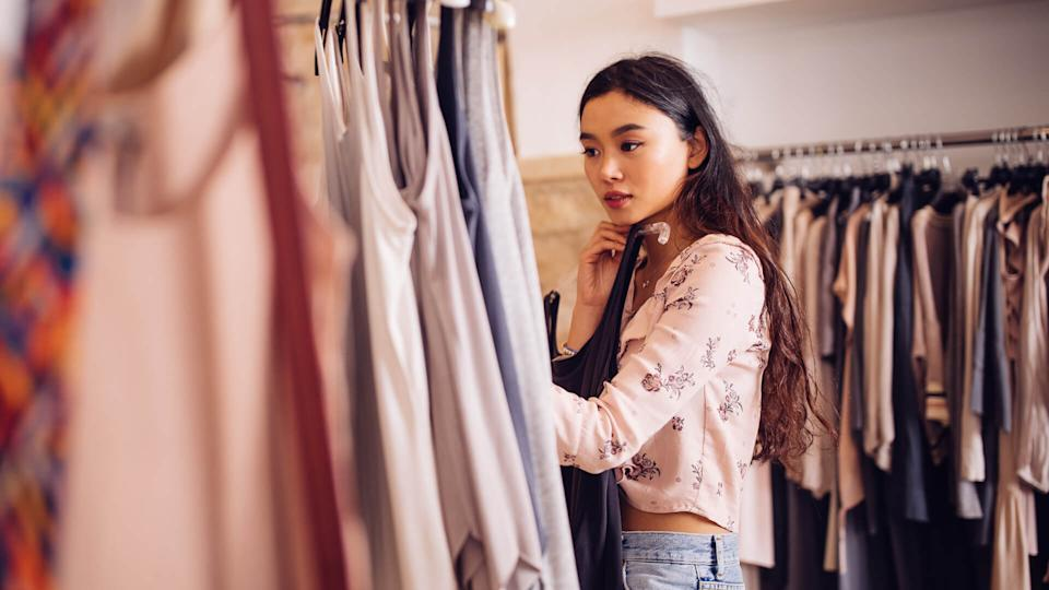 Beautiful young asian woman browsing and looking to buy summer clothes in a women's boutique.
