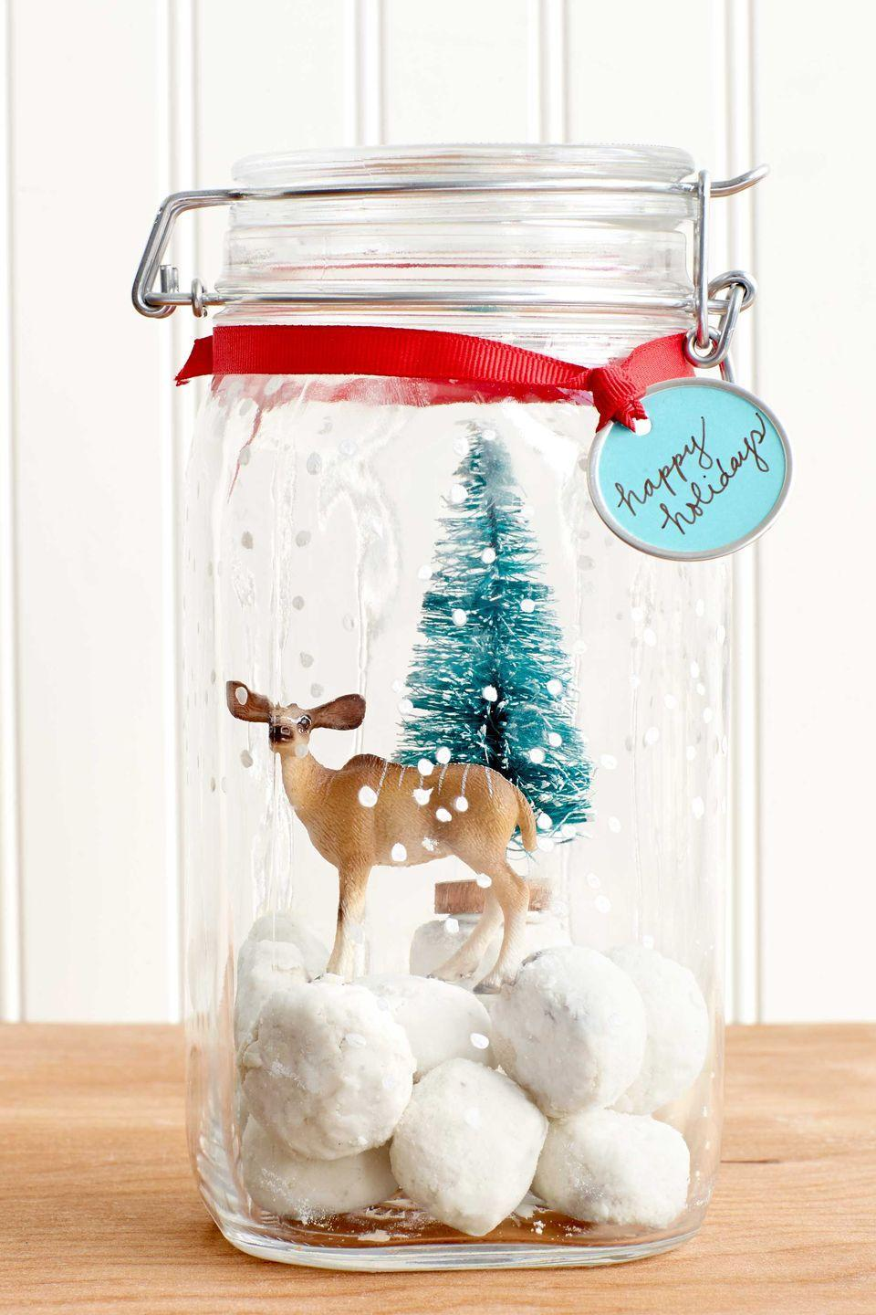 """<p>Skip the same-old tin and give cookies in a festive (airtight!) jar instead.</p><p><strong>Step 1:</strong> Use a fine-tipped brush to paint small white dots on the outside of a glass jar.</p><p><strong><strong>Step 2:</strong> </strong>Fill bottom of jar with <a href=""""https://www.countryliving.com/food-drinks/recipes/a5975/mexican-wedding-cookies-clx1014/"""" rel=""""nofollow noopener"""" target=""""_blank"""" data-ylk=""""slk:snowball cookies"""" class=""""link rapid-noclick-resp"""">snowball cookies</a>. Place small plastic trinkets inside for a snow globe-inspired vignette.</p><p><strong>Step 3:</strong> Tie gift tag to jar with ribbon.<br></p><p><a class=""""link rapid-noclick-resp"""" href=""""https://www.amazon.com/32oz-Regular-Mouth-Canning-Mason/dp/B01N6QBJG0?tag=syn-yahoo-20&ascsubtag=%5Bartid%7C10050.g.647%5Bsrc%7Cyahoo-us"""" rel=""""nofollow noopener"""" target=""""_blank"""" data-ylk=""""slk:SHOP MASON JARS"""">SHOP MASON JARS</a><br></p>"""
