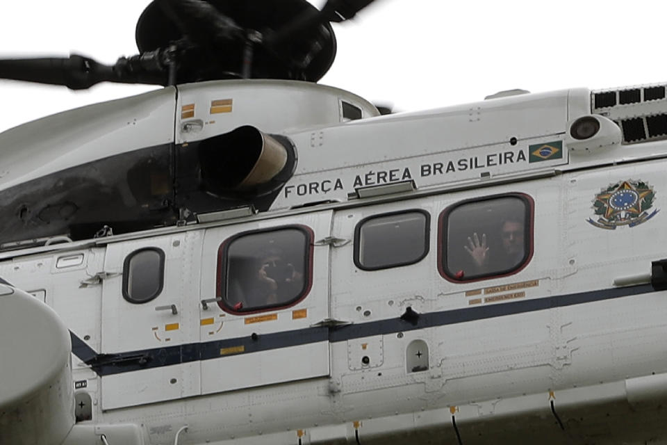 Brazil's President Jair Bolsonaro waves to supporters from the presidential helicopter flying over a demonstration backing Bolsonaro's anti-coronavirus-lockdown stance, marking May Day, or International Workers' Day, in Brasilia, Brazil, Saturday, May 1, 2021. (AP Photo/Eraldo Peres)