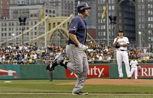 San Diego Padres' Chase Headley, left, runs past Pittsburgh Pirates starting pitcher A.J. Burnett after hitting a home run off him in the first inning of the baseball game on Saturday, Aug. 11, 2012, in Pittsburgh. (AP Photo/Keith Srakocic)